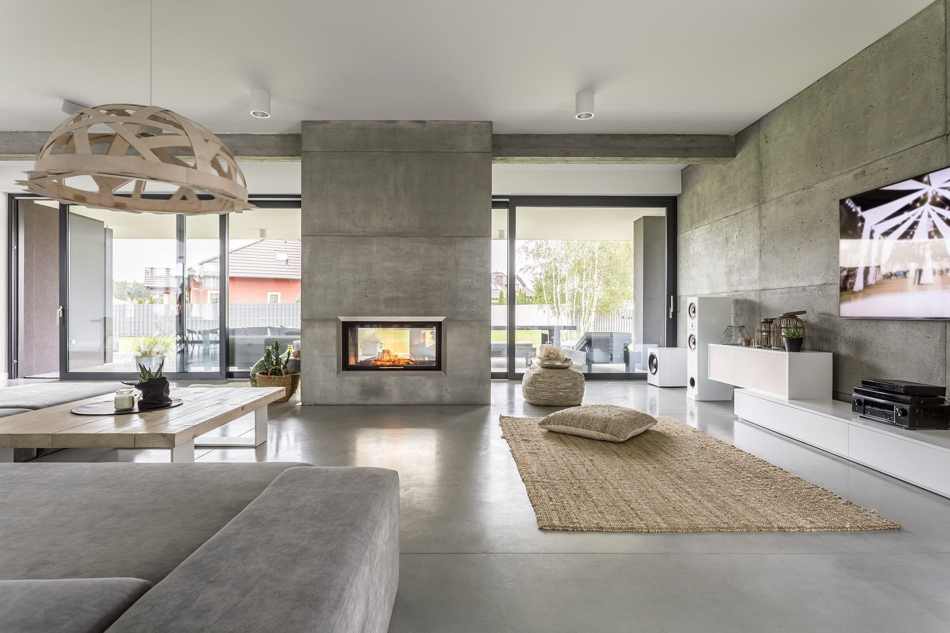 Salon con sofà, tavola bassa di legno,camino e le pareti e il suolo di geopietra