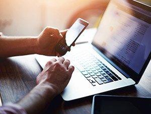 Uomo che scrive su un telefono davanti un laptop