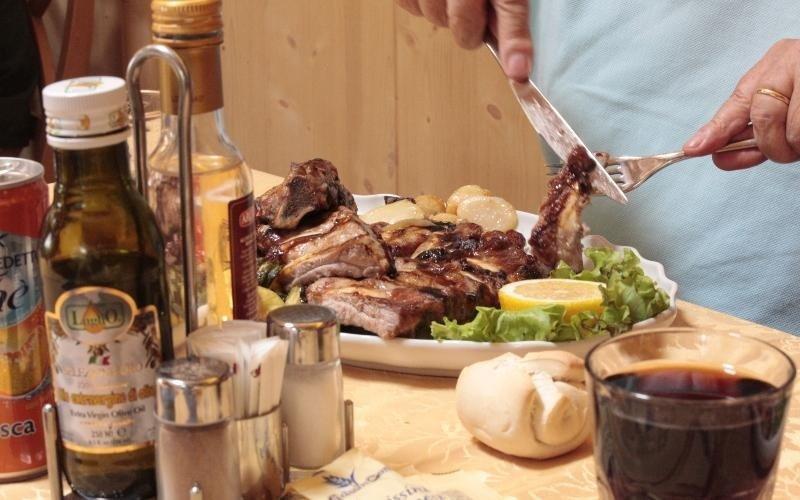 piatto di carne sul tavolo con vari condimenti a parte