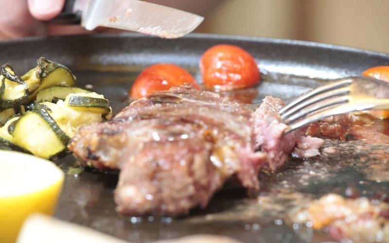 bistecca sul piatto che viene inforchettata