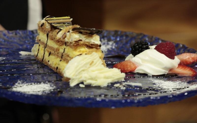 piatto con fetta di torta alla crema con panna a lato