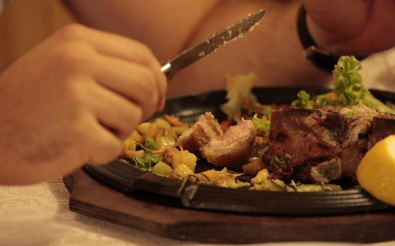 persona che sta mangiando un piatto di carne