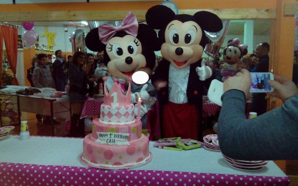 Mickey Mouse e Minnie Mouse davanti alla torta di compleanno
