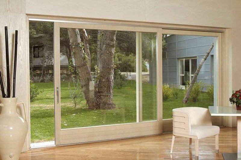 sala con parquet in legno chiaro una sedia in pelle bianca, un tavolino con dei fiori rossi e una porta finestra con vista del giardino