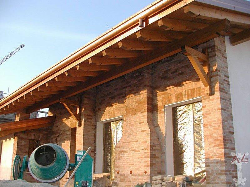 esterno di una casa in mattoni, tetto in legno e nel giardino una betoniera per il cemento di color verde