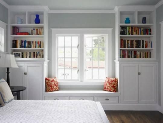 camera da letto con armadio libreria da entrambi i lati della finestra, il tutto di color bianco e un tavolino con una lampada nera
