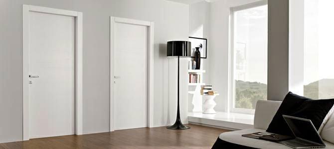 soggiorno con due porte di color bianco, u na lampada nera, si intravede il divano con appoggiato sopra un computer portatile
