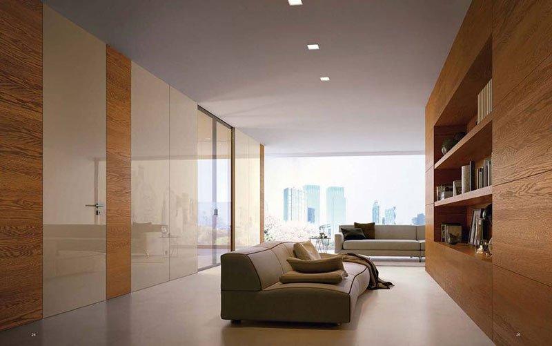 living con divano in pelle color crema sulla destra un mobile in legno con delle mensole e sul lato sinistro un grande armadio con porte in color bianco e noce