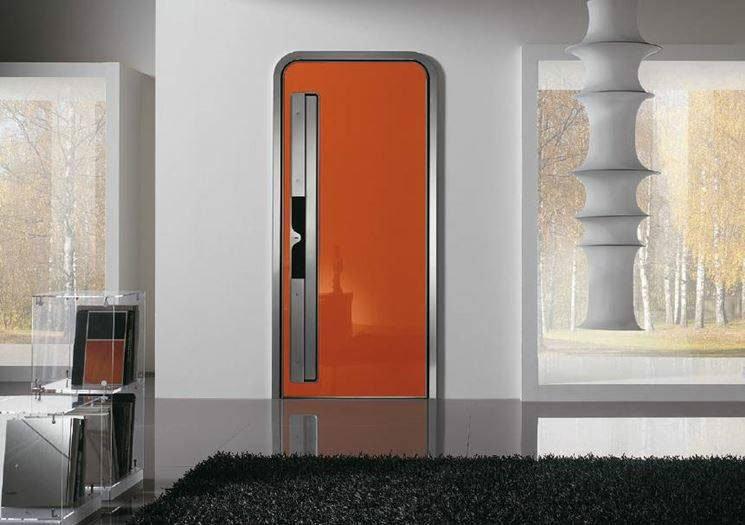 vista di una stanza con una porta arancione un tappeto nero e sulla destra una colonna bianca davanti alla finestra