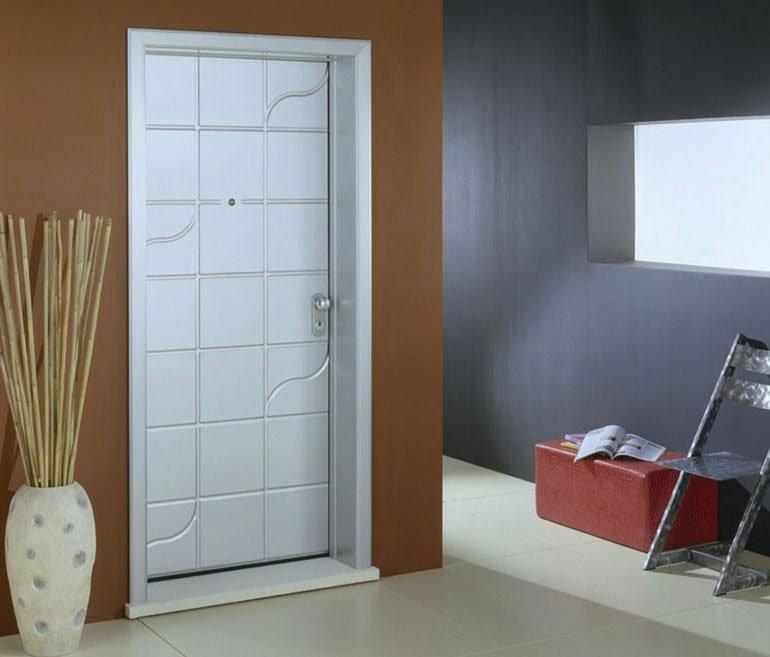 porta di color bianco, un vaso con dei bastoni di bambu', sulla destra una sedia in metallo e un puff rosso con sopra delle riviste