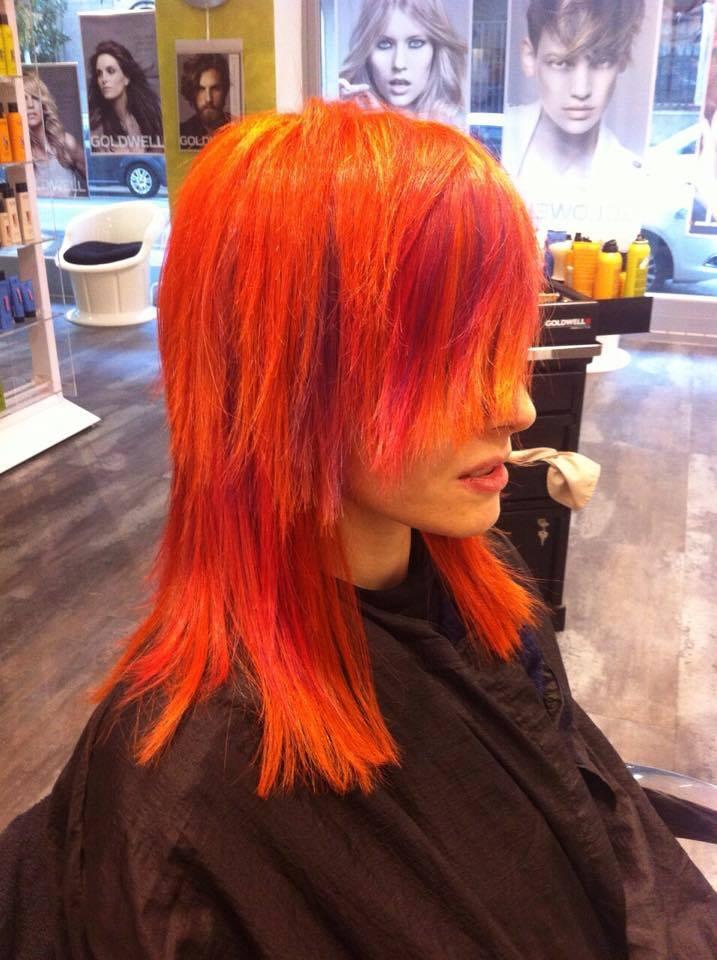 Una donna seduta sulla poltrona in un parrucchiere con capelli tinti di arancione