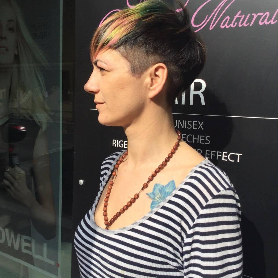 Una donna con capelli rasati sui lati e lunghi in mezzo tinti in verde e rosa