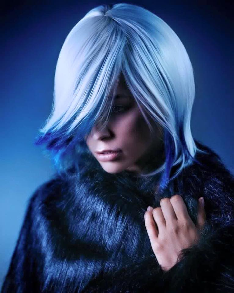 Una donna con una pelliccia nera e capelli tinti in grigio chiaro e sulle punte in color viola