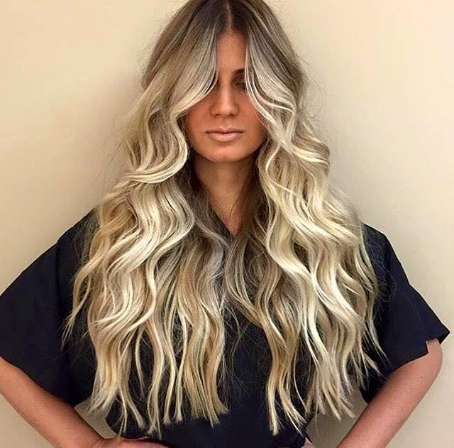 Una donna con capelli mossi e tinti di biondo