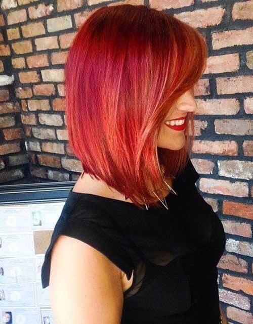 Una donna con un vestito nero e capelli tinti di rosa e rosso