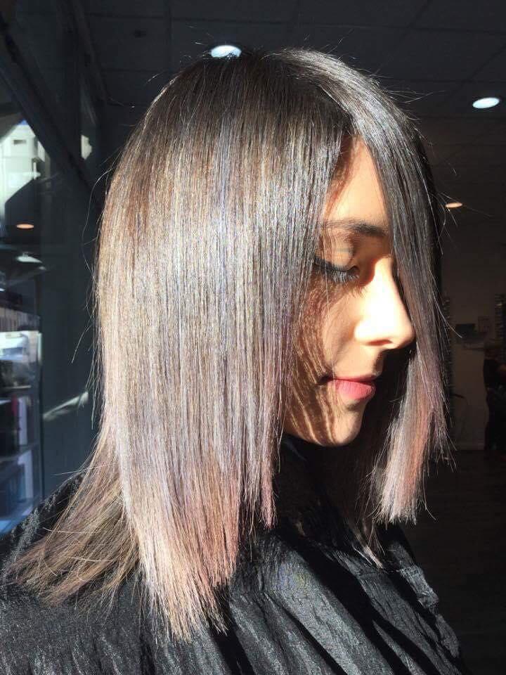 Una donna con capelli neri e meches di color castano scuro