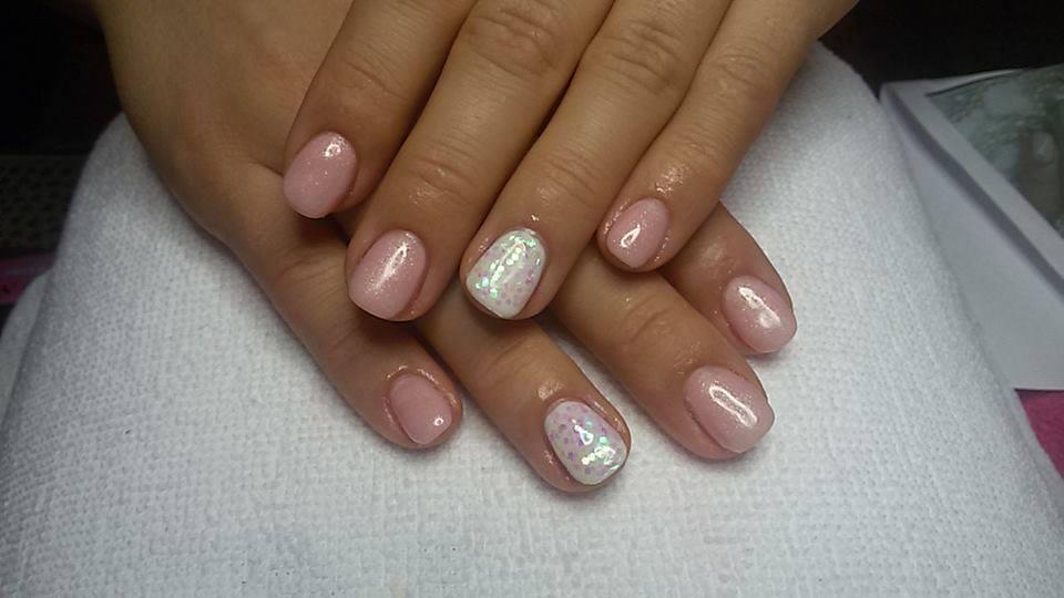 Mani di una donna con le unghie con uno smalto di color rosa e bianco con brillantini