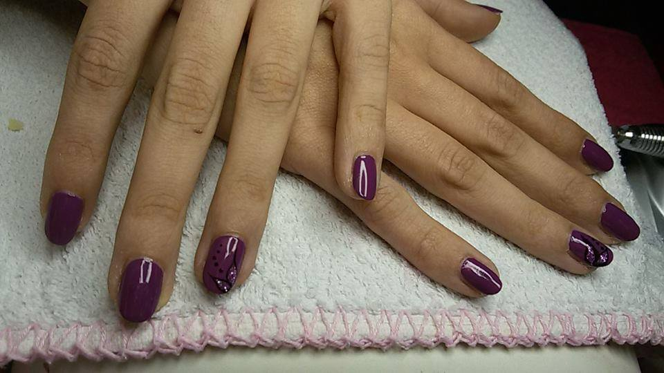 Delle mani con uno smalto viola e una unghia con disegni nere