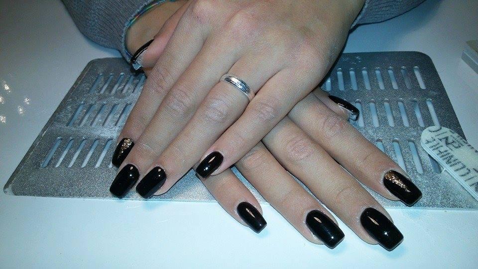 Mani di una donna con le unghie con smalto di color nero