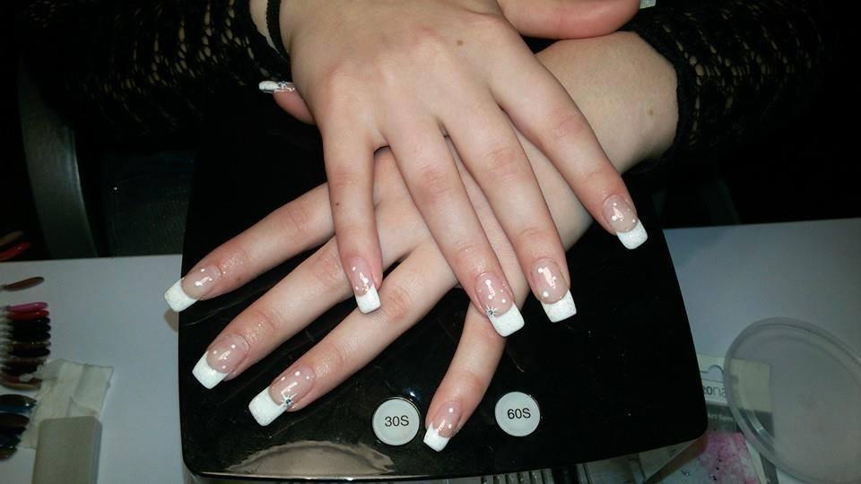 Unghie di una donna con mani con manicure francese