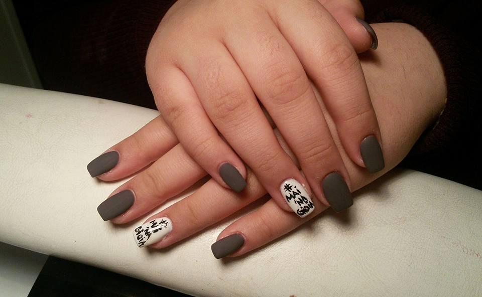 Mani di una donna con smalto di color grigio e bianco