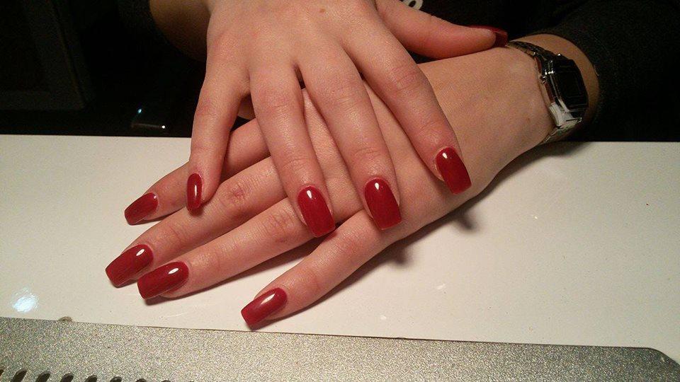 Mani di una donna con le unghie con lo smalto di color rosso
