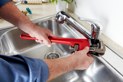 expert plumber is installing a sink in kithcen