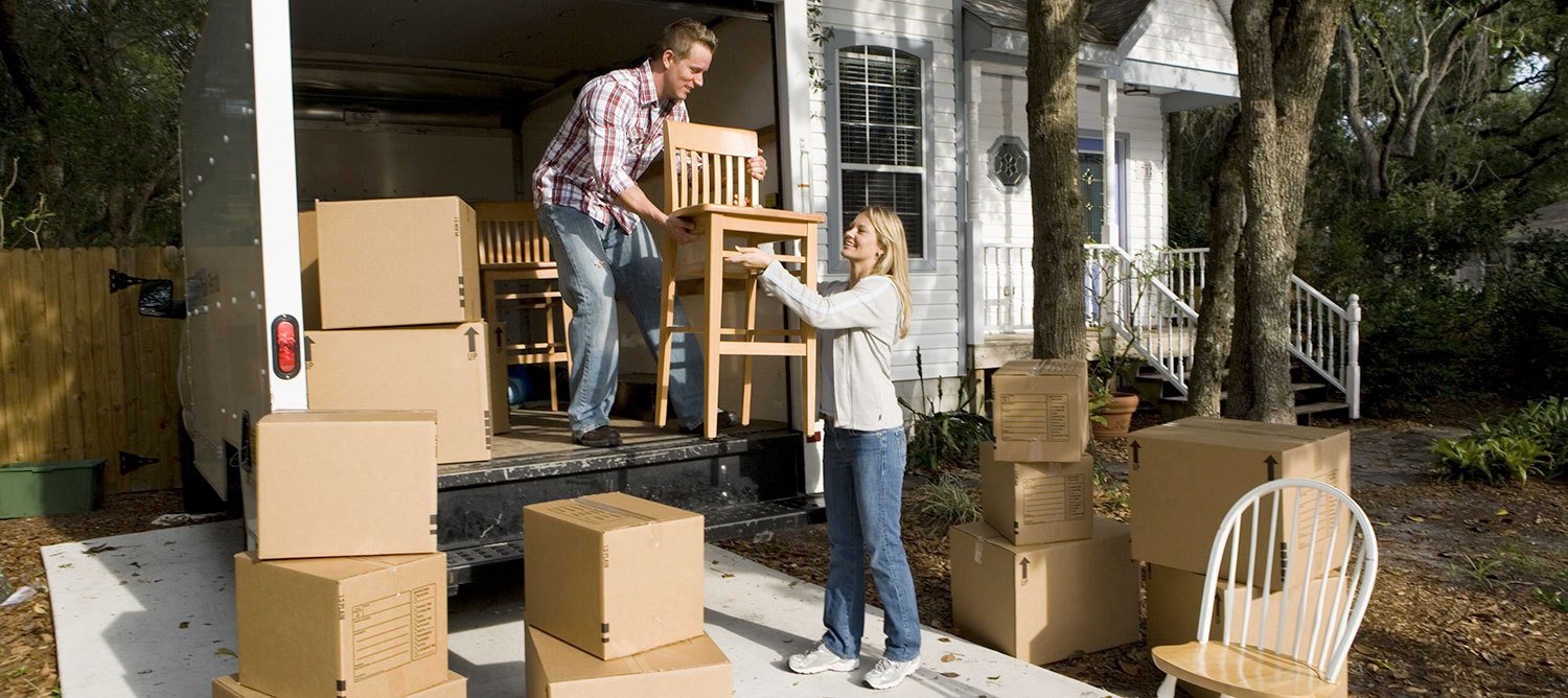 Image Of A Couple Removing Boxes And Chairs From Their Long Distance Moving  Truck