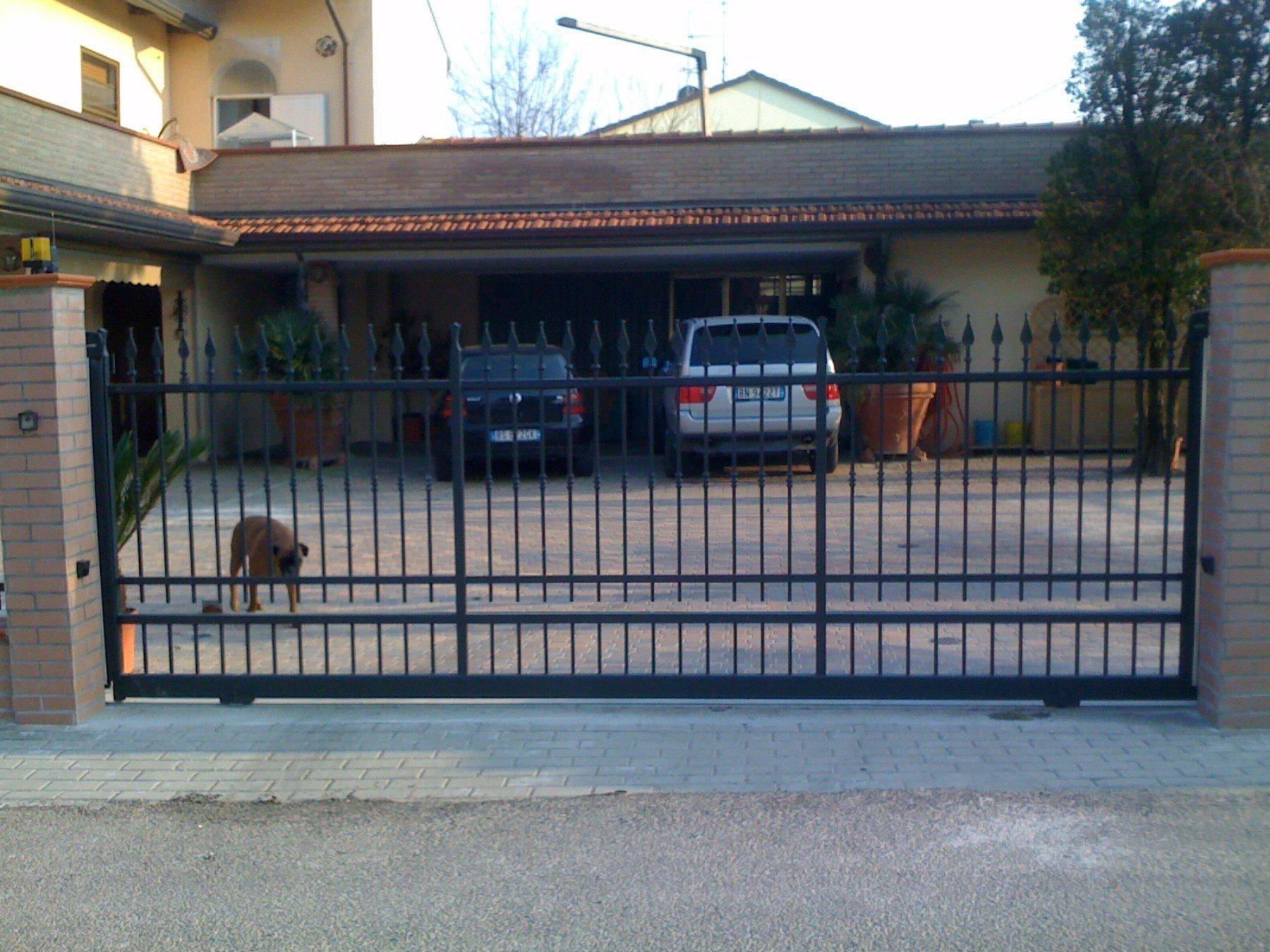 un cancello di una villa con delle macchine parcheggiate