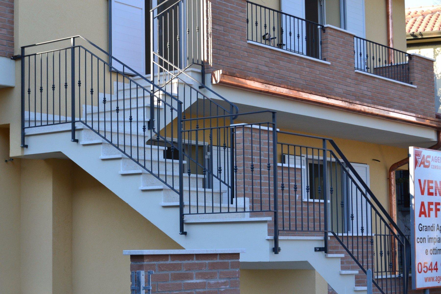 delle scale con corrimano in ferro battuto nero