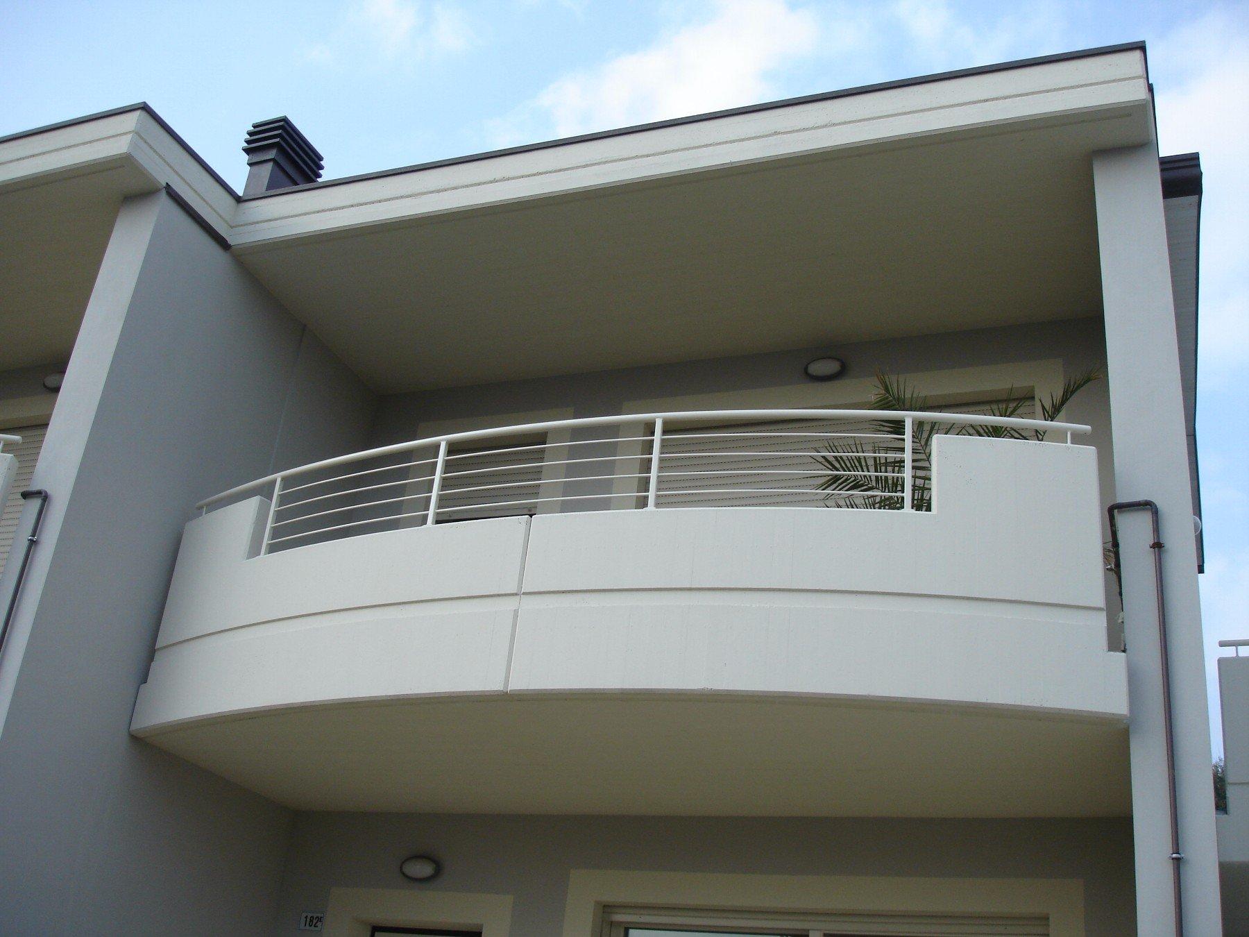 un balcone bianco con una ringhiera in ferro battuto