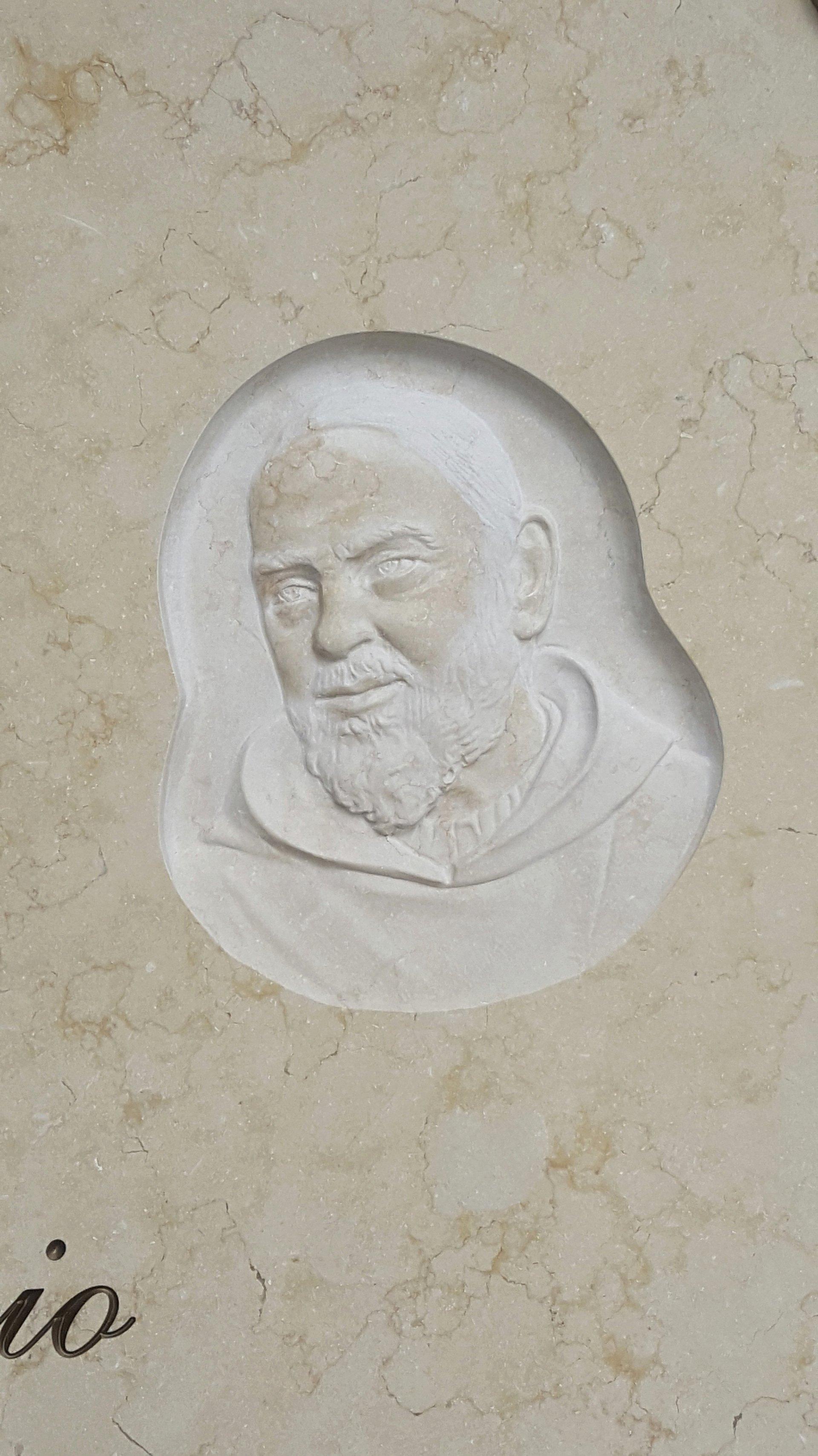 bassorilievo su marmo beige rappresentante padre pio