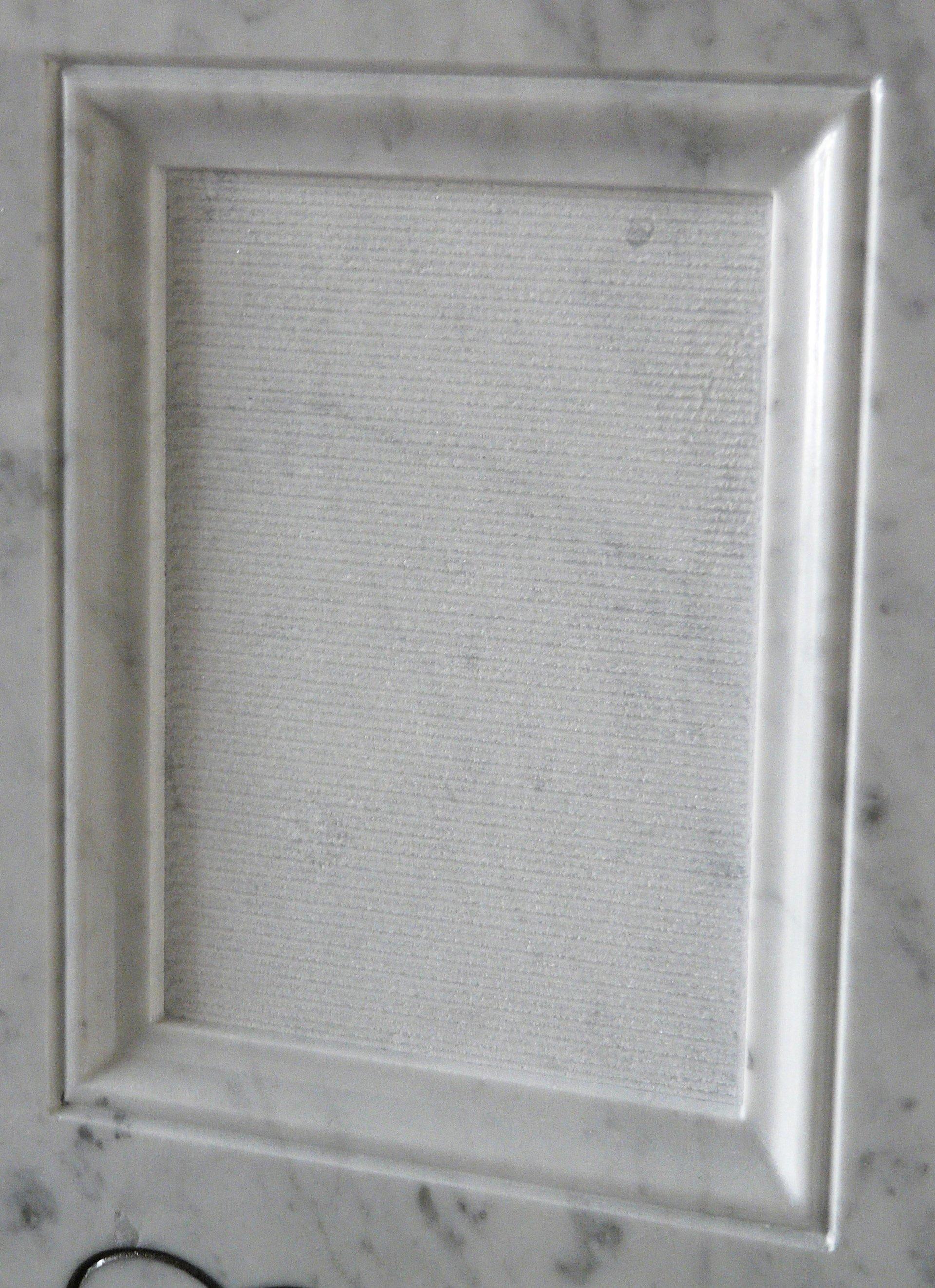 bassorilievo su marmo bianco rappresentante una cornice