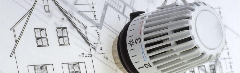 una manopola di una valvola di un termosifone e accanto un disegno di un progetto di una casa