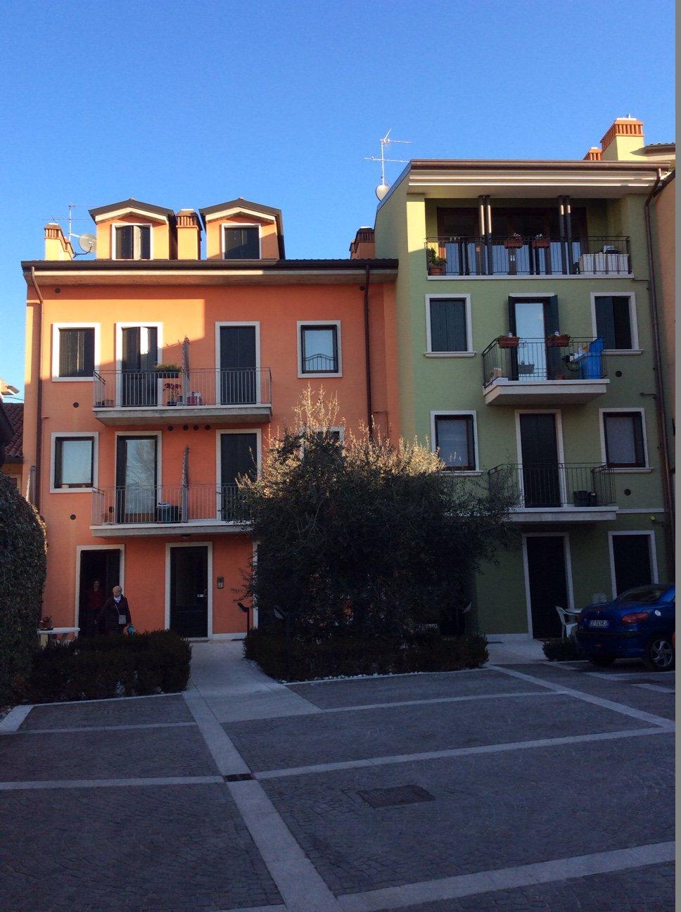 un condominio arancione e uno verde attaccati
