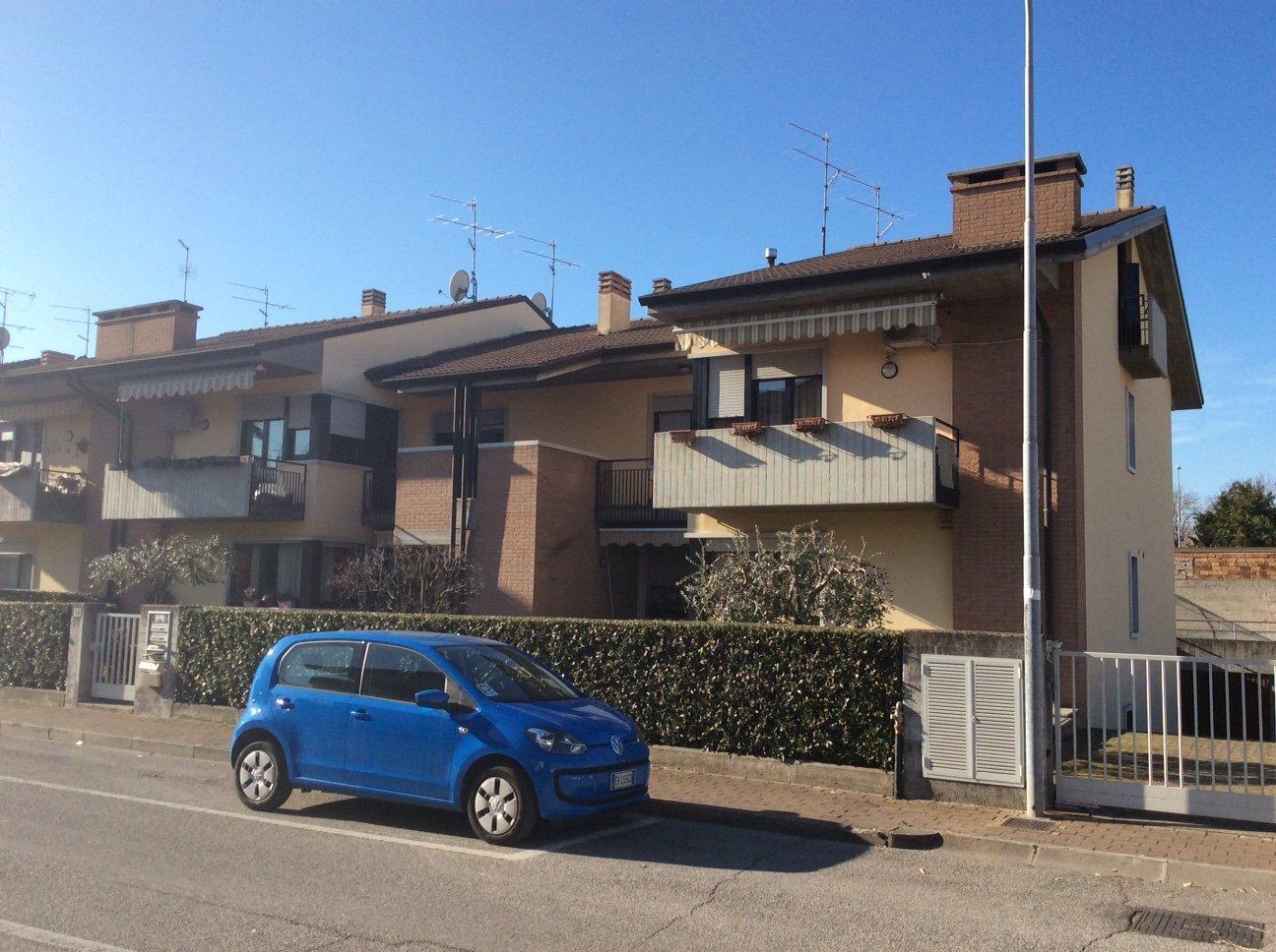 costruzione appartamenti indipendenti con auto blu parcheggiata vicino alla siepe