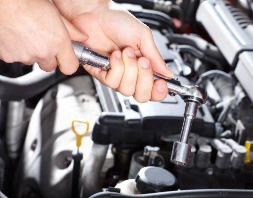 due mani con un attrezzo che svitano i bulloni di un motore