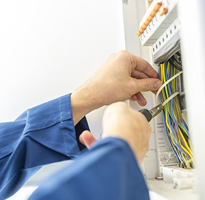 Electrician installing an electrical fuse box