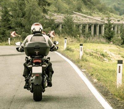 Man riding motorcycle along road