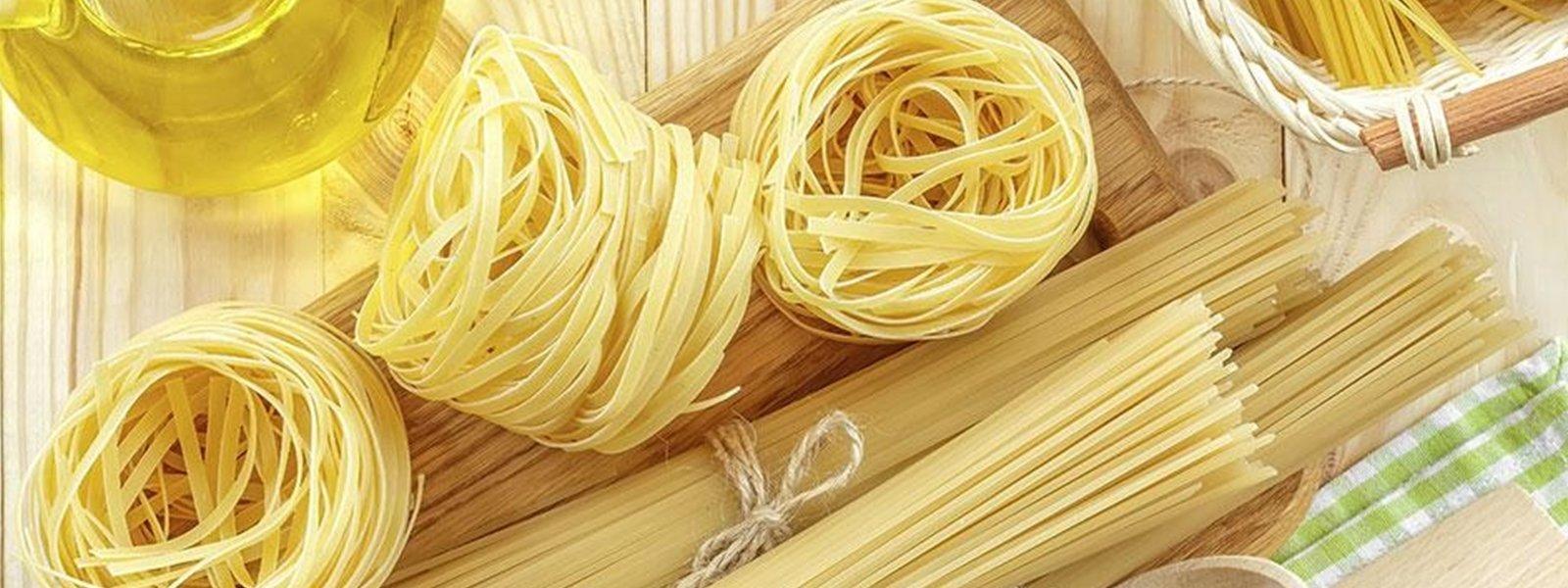 delle tagliatelle, degli spaghetti e altro su un tavolo di legno