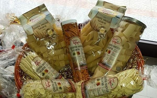 un cesto con delle confezioni e dei barattoli con dentro della pasta