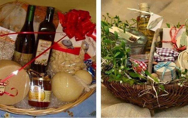 due cestini natalizi uno con confetture, pasta, vino e un fiocco rosso e l'altro con delle confezioni a quadretti di diversi colori