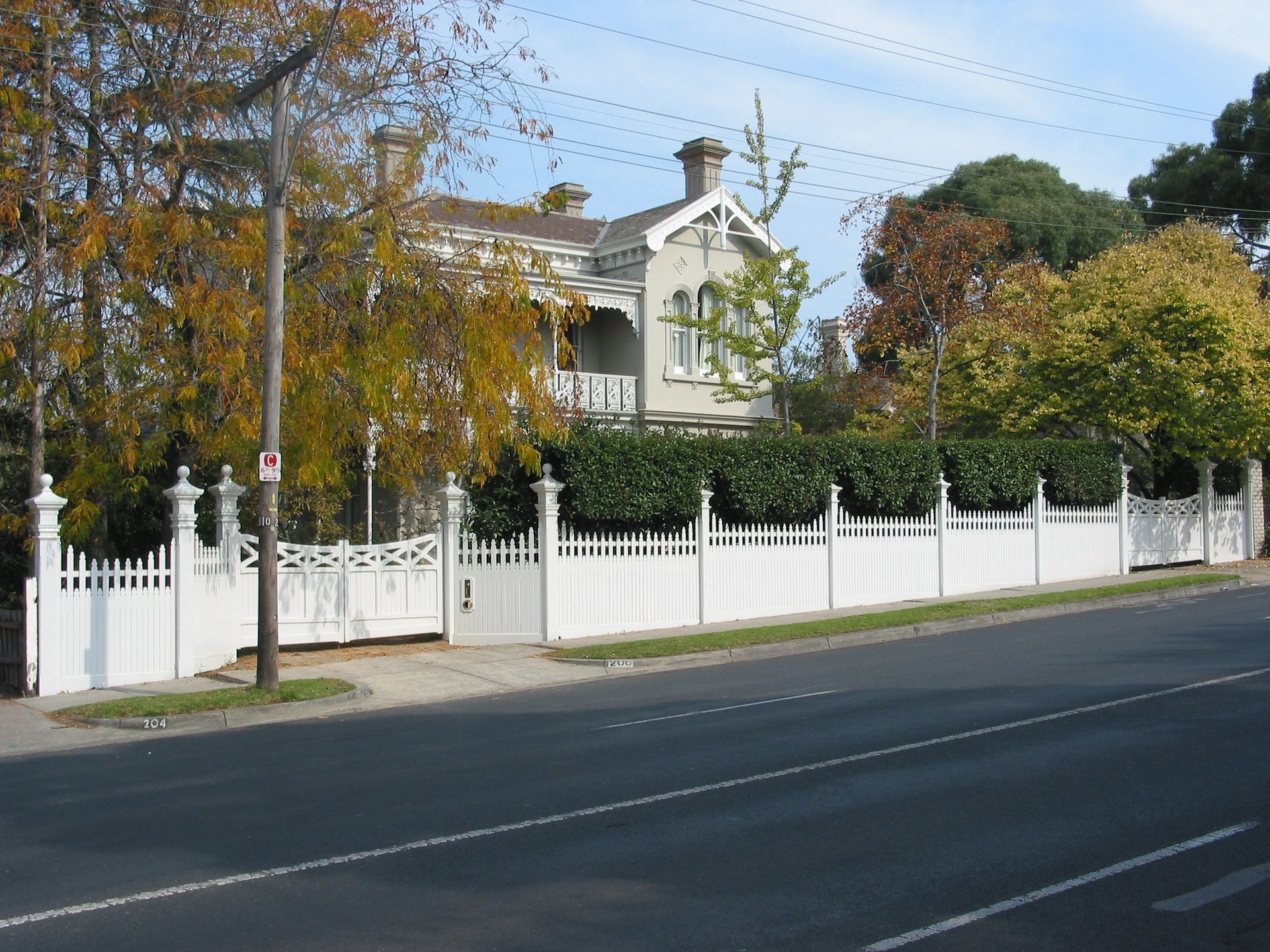 White timber picket fence and driveway swing gate by Perry Bird Pickets