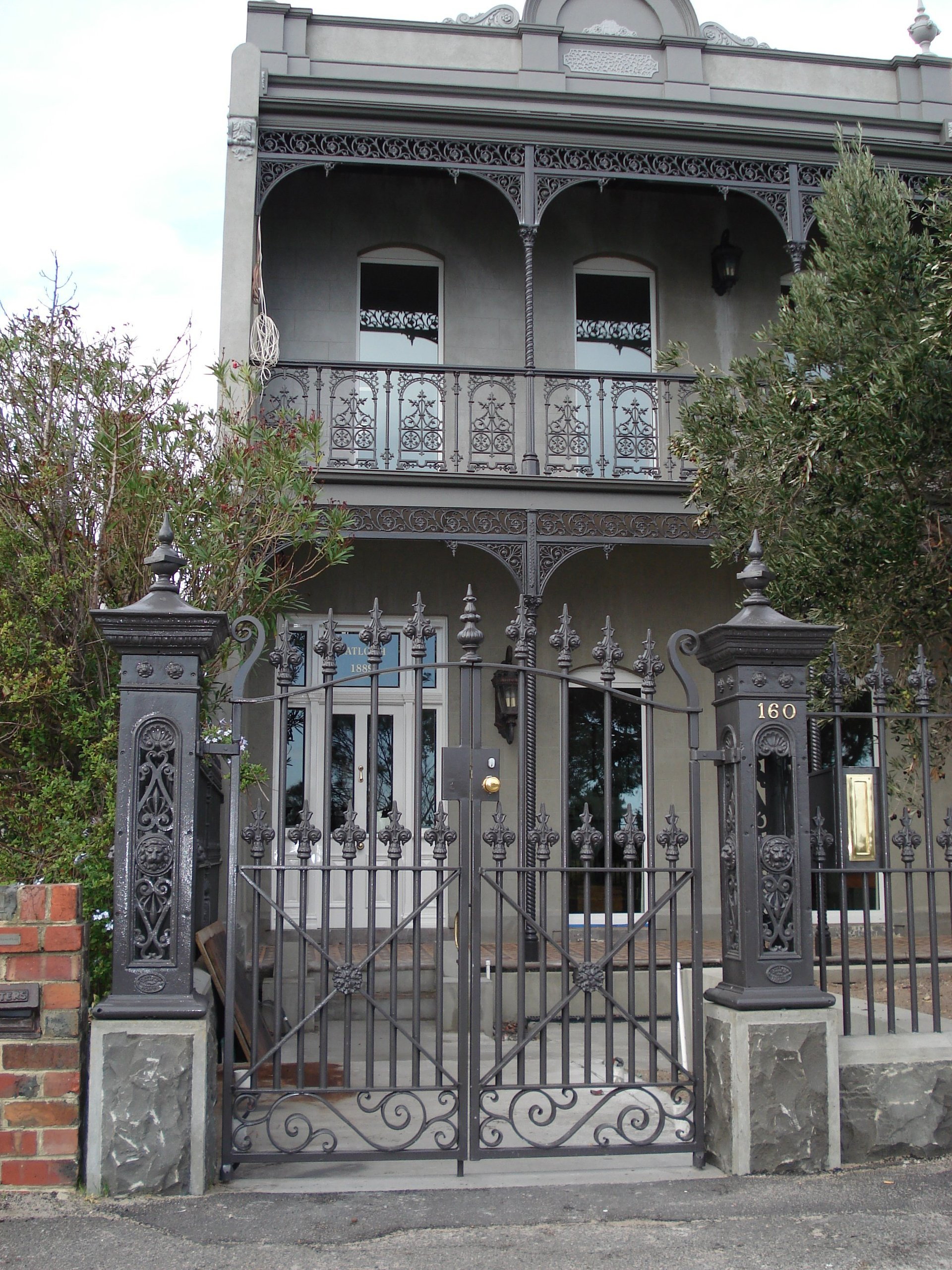 Timber pedestrian gate with cast iron capitals on timber posts by Perry Bird Pickets