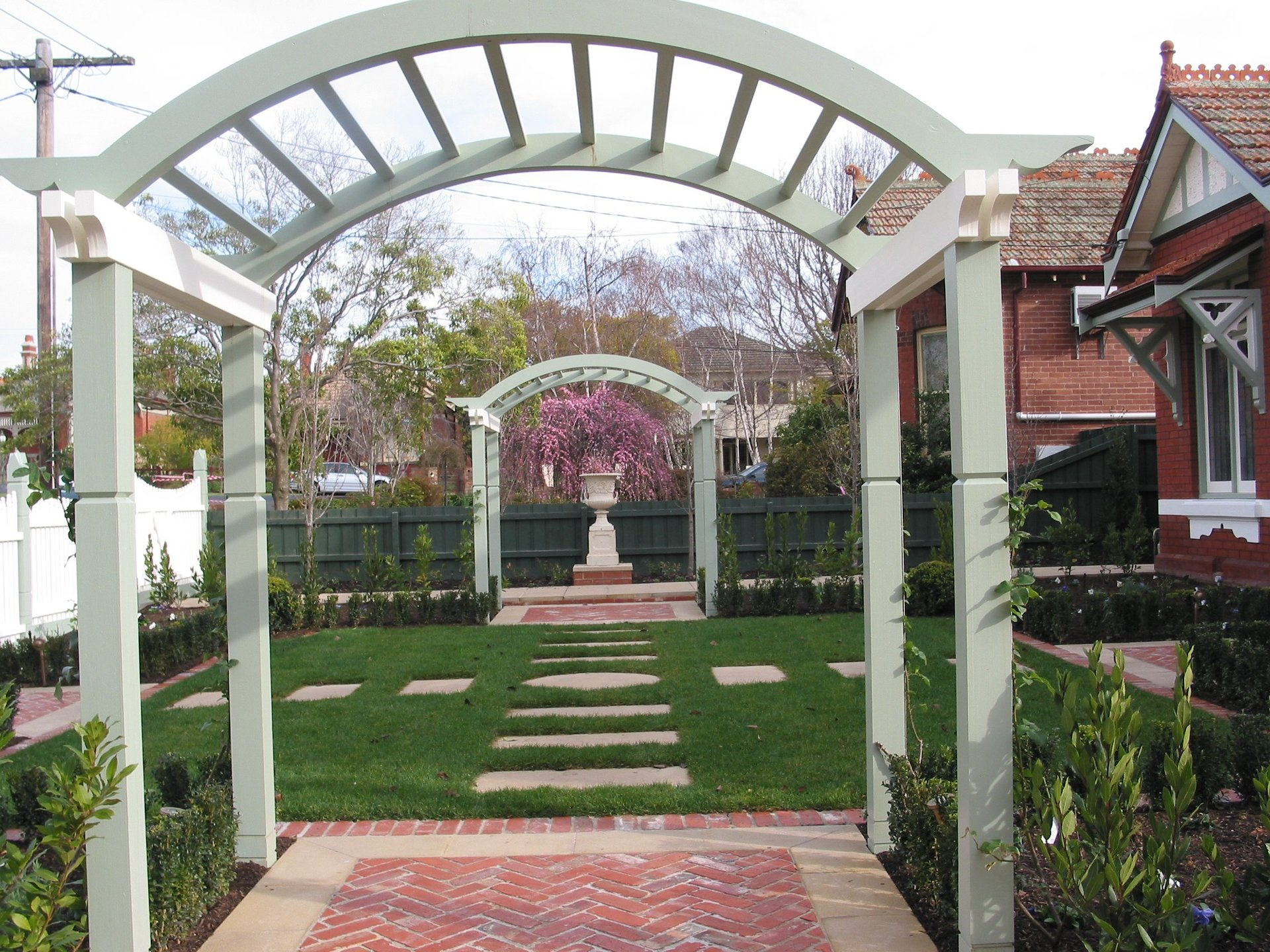 Feature archways in backyard by Perry Bird Pickets