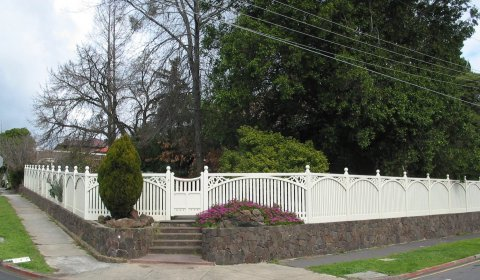 white fence and feature gate with trees and garden