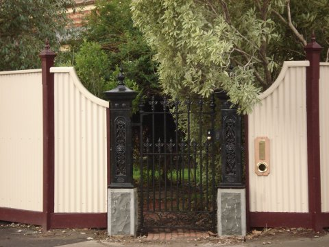 maroon and white fence with cast iron gate