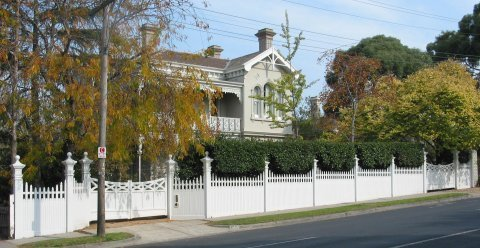 white picket fence around large mansion