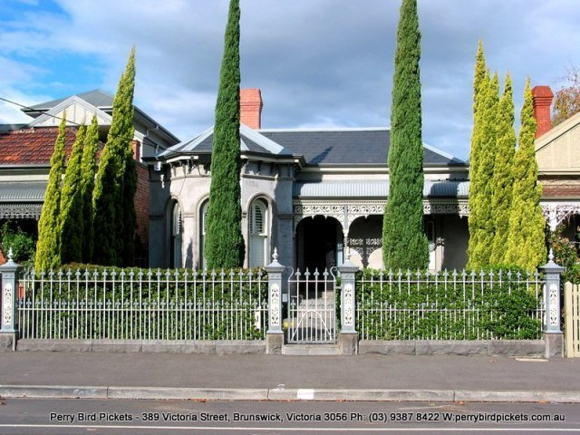 cast iron fence with manicured garden