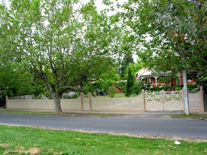 off white fence and gate with trees